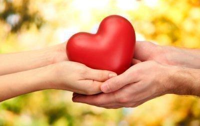 Пара держит сердечко в руках
