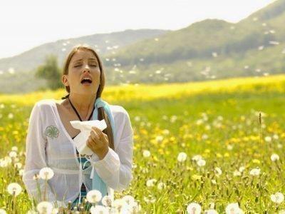 Женщина чихает на лугу
