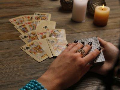разложенные на столе карты и женская рука