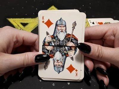 В женских руках колода с бубновым королем сверху