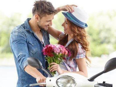 Сексуальная пара с цветами на мотоцикле