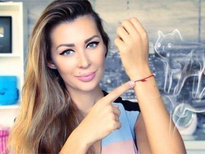 Девушка показывает на красную нить на запястье