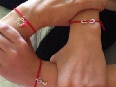 Три кисти руки с красной нитью и амулетами