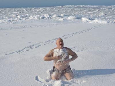 Мужчина растирается снегом