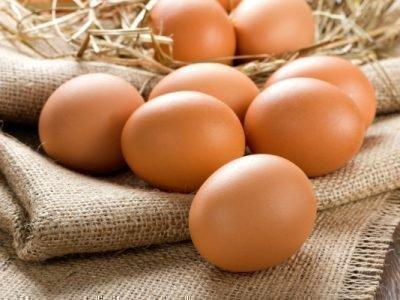 Куриные яйца на мешковине с соломой