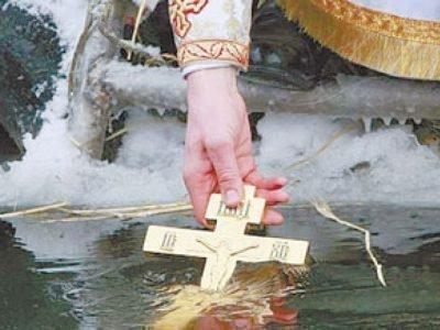Рука с крестом, опущенным в воду