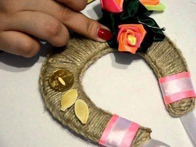 Подкова с цветочками и пальцы женской руки