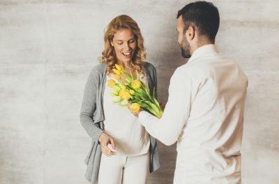 Мужчина дарит желтые тюльпаны