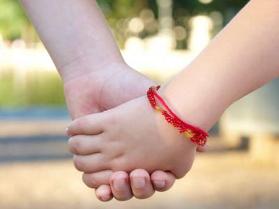 Две руки , на одной из которых браслет из красной нити