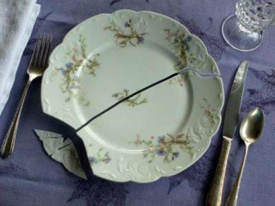 Треснувшая тарелка, нож, ложка и вилка на столе