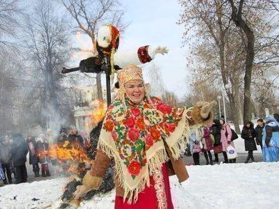 Женщина танцует перед горящим чучелом Масленицы