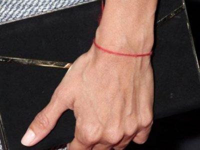 Рука с блокнотом и красной нитью на запястье