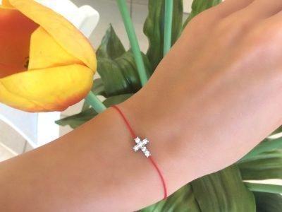 Рука с цветами, на запястье крестик на красной нитке